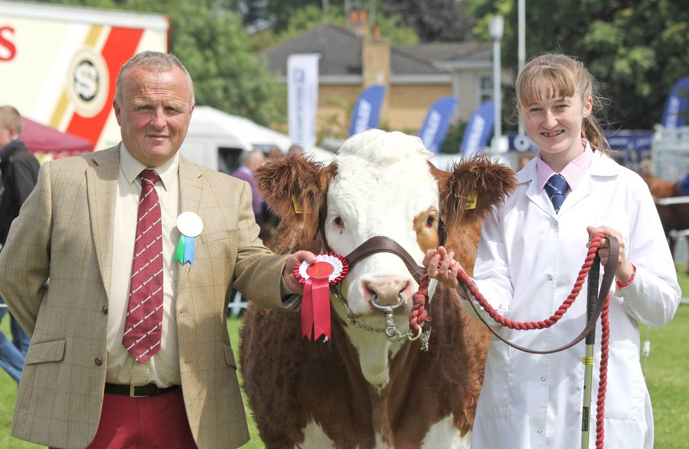 Molly Bradley, Armagh, was the winner of the senior young handler class at the NI National Simmental Show. Included is British Simmental Cattle Society Michael Barlow who judged at the Omagh event.